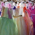 An array of colorful little girl's party or princess dresses for sale at outdoor vendor