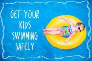 Little Girl In Swimming Pool On Inflatable Ring