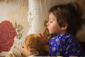 Adorable little boy sleeping at night with his teddy bear friend